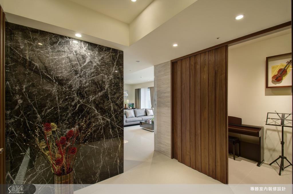 利用木紋門板作為隱藏門片,讓原本開放式的空間,立即變身成為音樂室與書房空間。