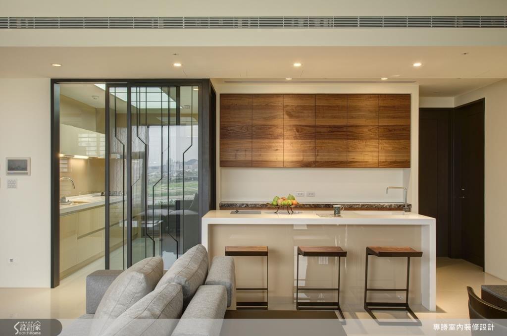 在餐廚兩者空間搭配上吧檯,豐富餐廚空間的機能性,此外為了建立起廚房與公共空間的區隔,更利用清玻璃與鐵件打造出一扇屏障,帶有流線現代感的設計,突顯了空間的時尚感。