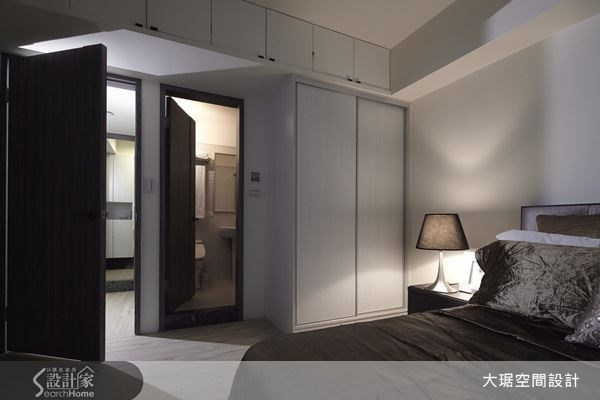 上方的大樑分別以下方的衣櫃、上方的收納櫃「夾攻」,既解決包樑後空間可能變矮的壓迫感問題,又增加收納空間,無形中拉高空間的長度,擴大視覺感。