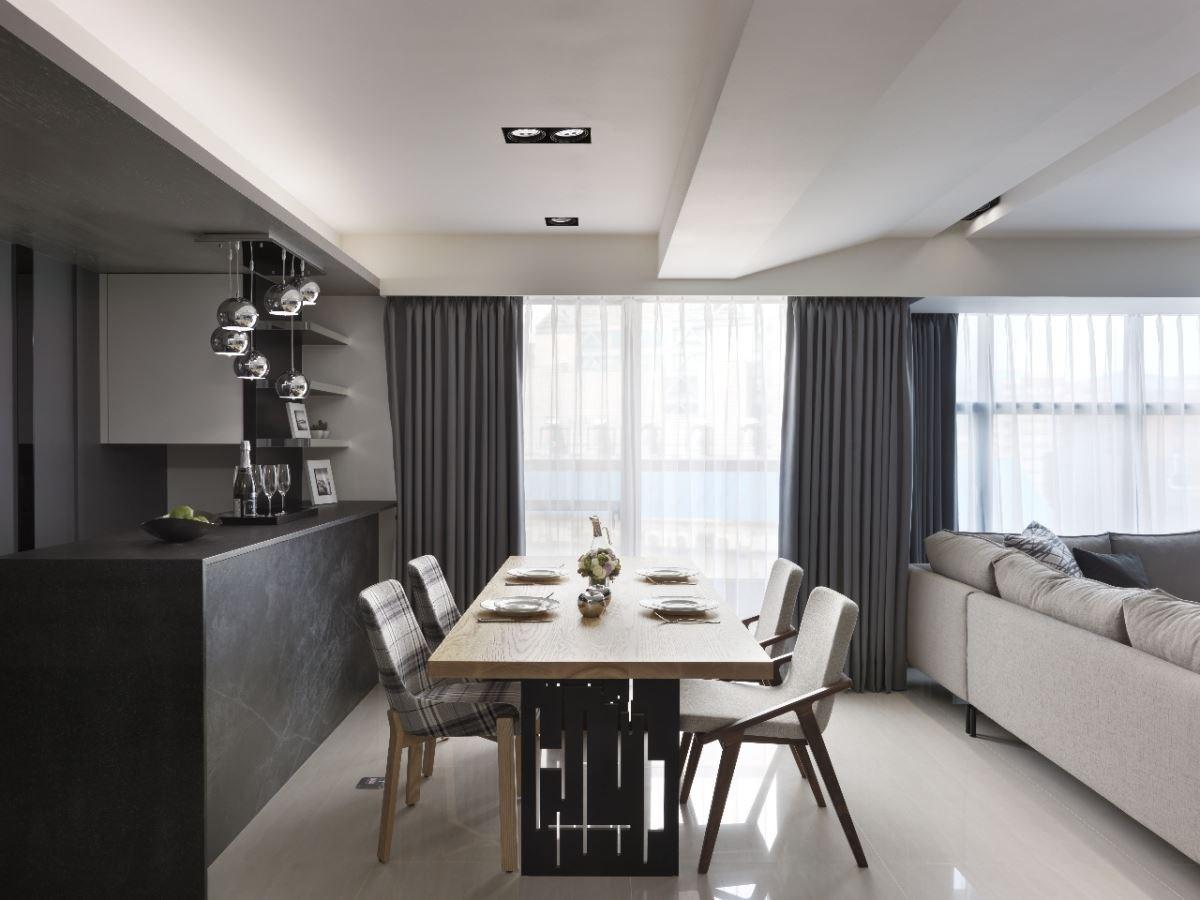 淺色餐桌與鐵件鏤空的桌腳,與黑色層板與鏡面組成的吧台,搭配屋主精心收藏的燈具,形成有趣的對比與呼應。