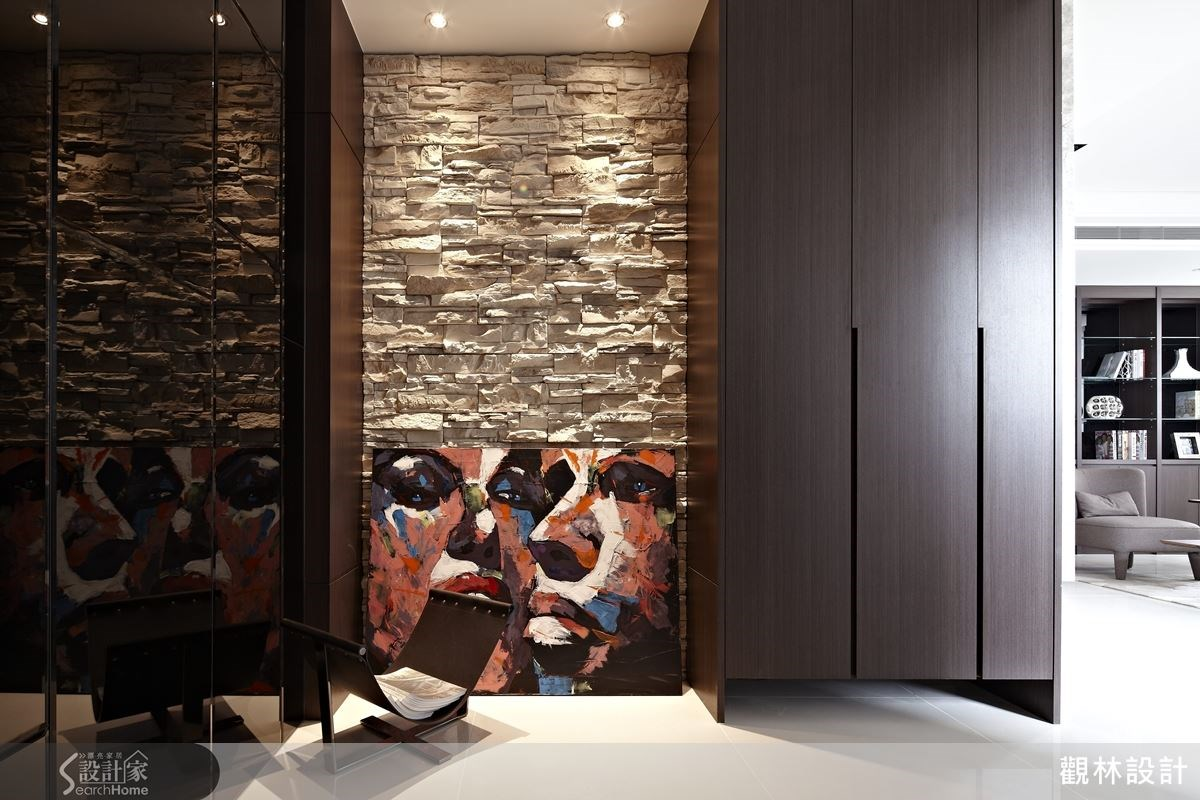 玄關處以淺色文化石搭配深色木櫃,型塑出自然大器的視覺觀感,而黑色鏡面給予人們空間放大的視覺感受,也能做整理儀容用,相當貼心的設計。
