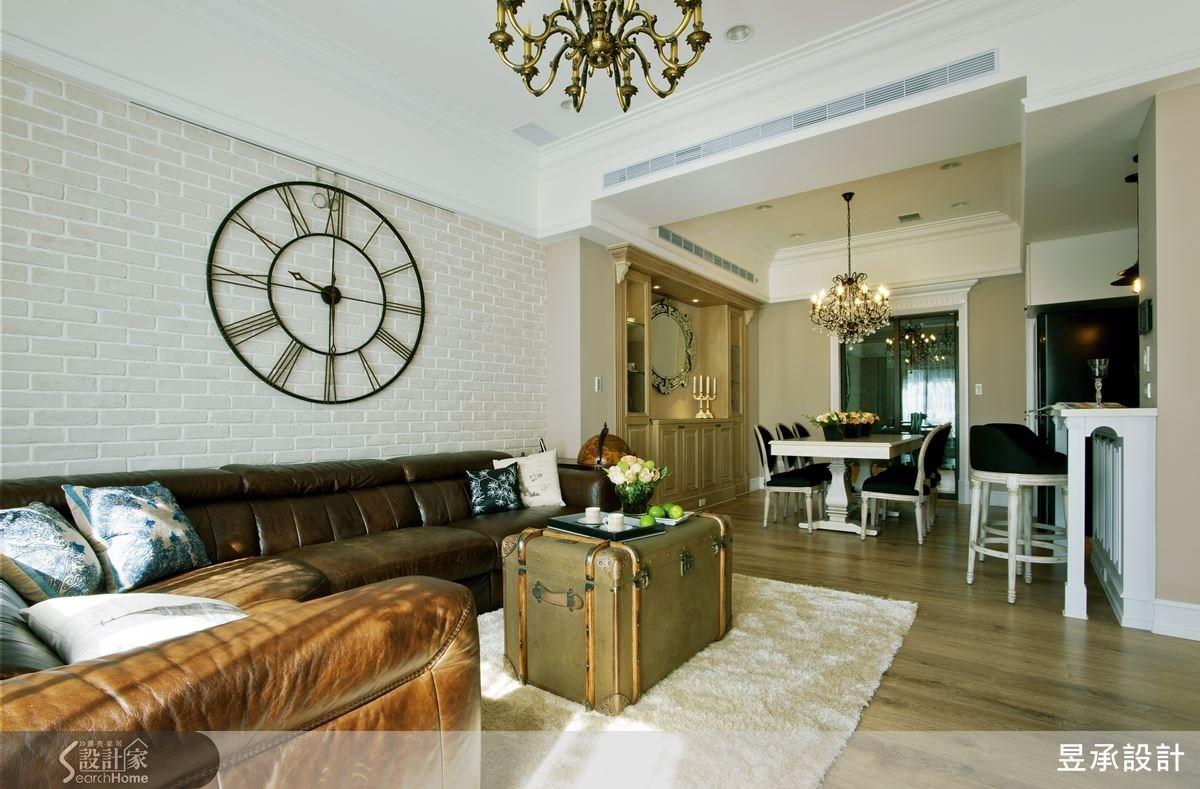 客廳運用文化石材質,突顯人文素雅氣息,品味極佳的屋主,挑選帶有美式風格的皮革沙發、皮箱造型茶几、大型復古風時鐘來妝點客廳,強化空間的主題感,同時也營造出一種旅行的氛圍。