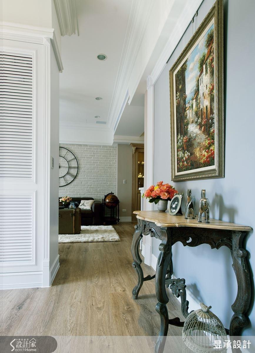 玄關區以灰藍色為主色調,帶出優雅沉穩的味道,牆上掛置大幅畫作,古典的木質桌擺上藝術品,襯出屋主的美學品味。