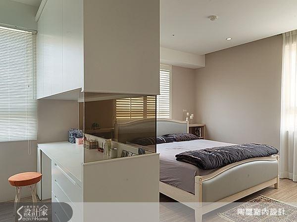 主臥室內部以一座化妝台兼收納櫃體將睡眠區與更衣室區分開來,櫃體中段使用茶色玻璃打造穿透式設計,讓櫃體不顯沉重而具有輕盈質感。