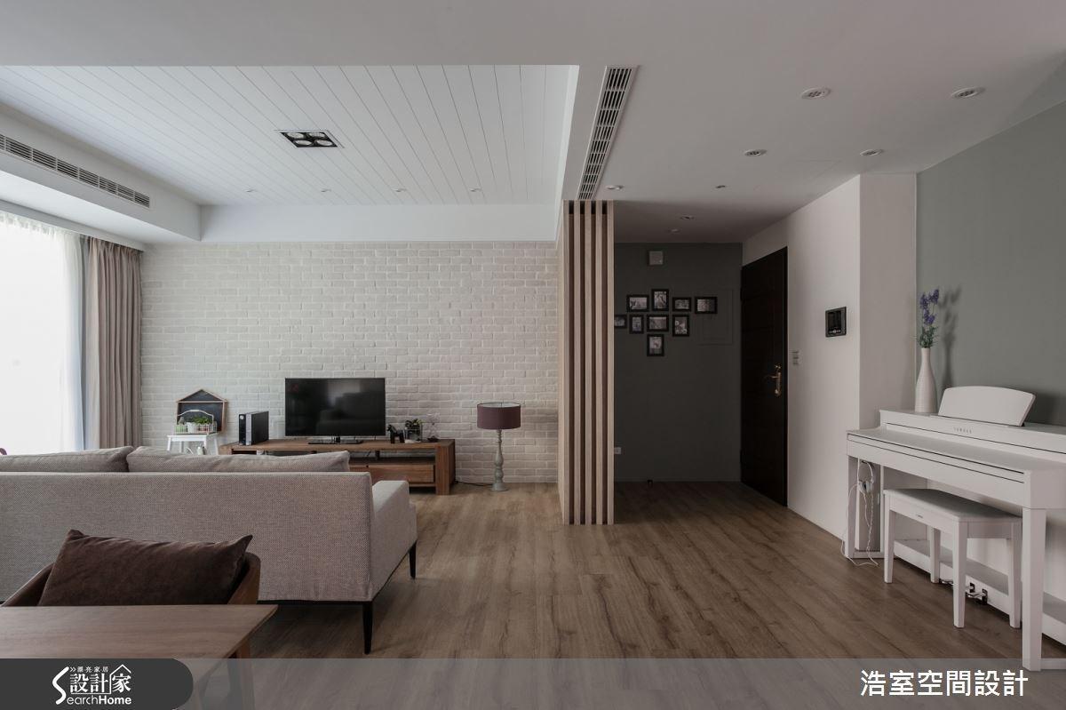 客廳電視牆面以白色文化石砌造而成,與深色家具和超耐磨地版整體搭配。