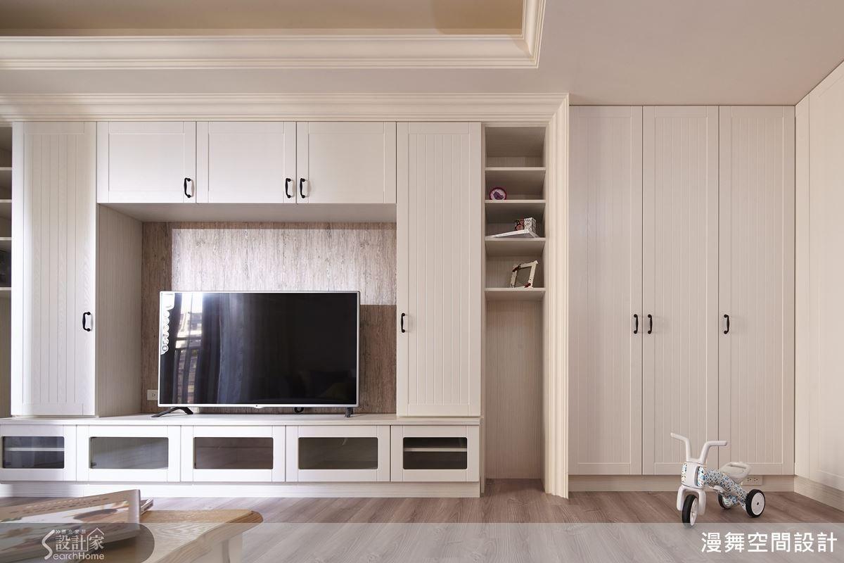 電視牆規劃整面的白梣木系統櫃,門片上綴以木工的邊框造型,與電視後方的木紋壁紙相呼應,營