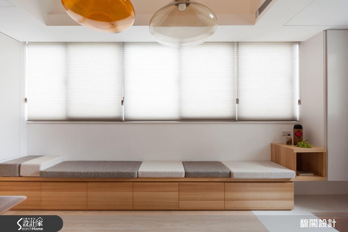 在靠窗處配置整排臥榻長椅,作為客人來訪時的座席,並搭配不同大小的椅墊,可隨時調整坐臥區域,並在檯面底部結合收納空間,滿足生活機能。