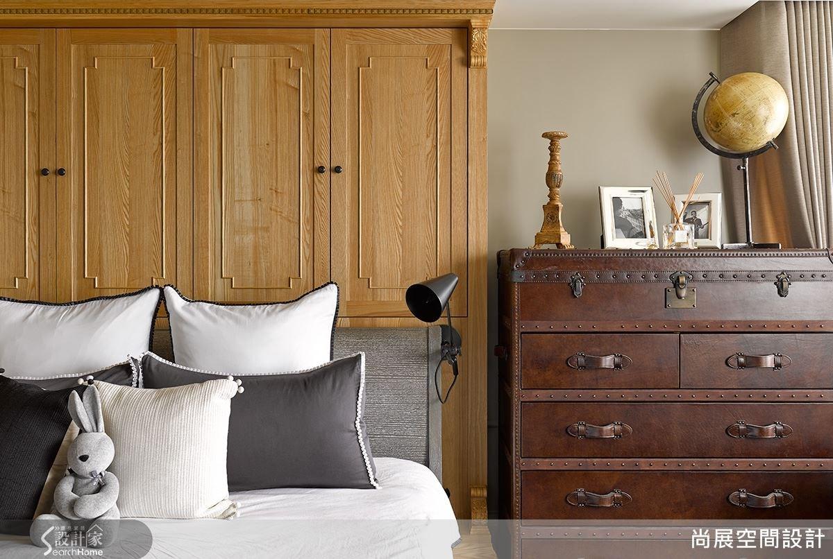 臥室採用行李箱元素設計的櫃子,在櫃子手把與櫃身上的鎖頭花紋特別講究,並擺放地球儀等旅行小物裝飾,配合臥室的整體旅行風格。