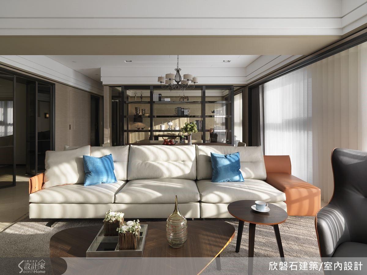 客廳沙發區是待客的要地。橘底、米白色沙發,點綴孔雀藍色系的抱枕。跳色與非成套的家具為空間帶來活潑感。