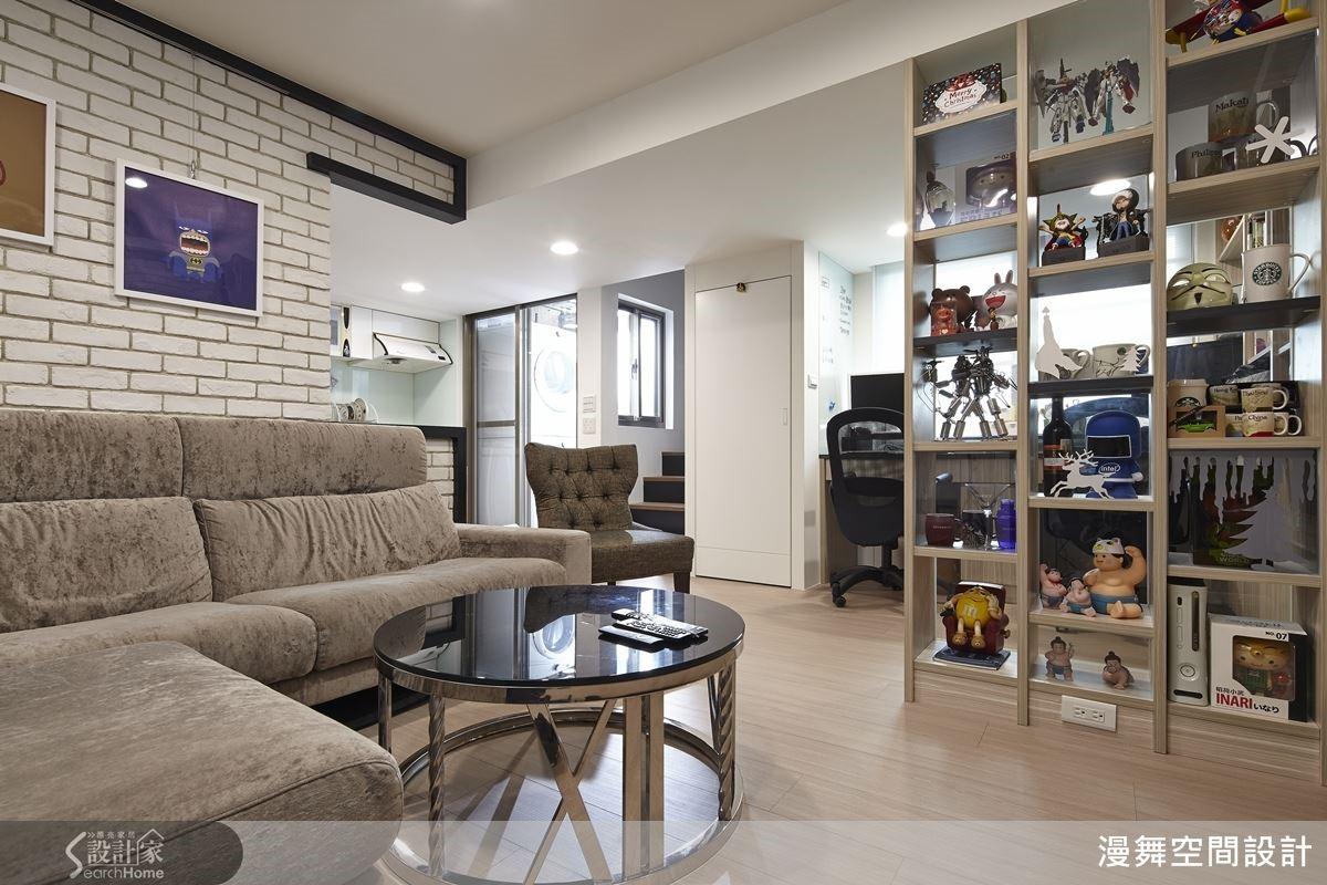 客廳和書房之間透過格子櫃區隔空間,讓空間的獨立性得以突顯之餘,亦保留光線和視線的穿透,帶來更為寬敞的空間感。而櫃體運用灰玻璃與清玻璃展現不同的鏡面效果,亦讓櫃子的造型更有趣。