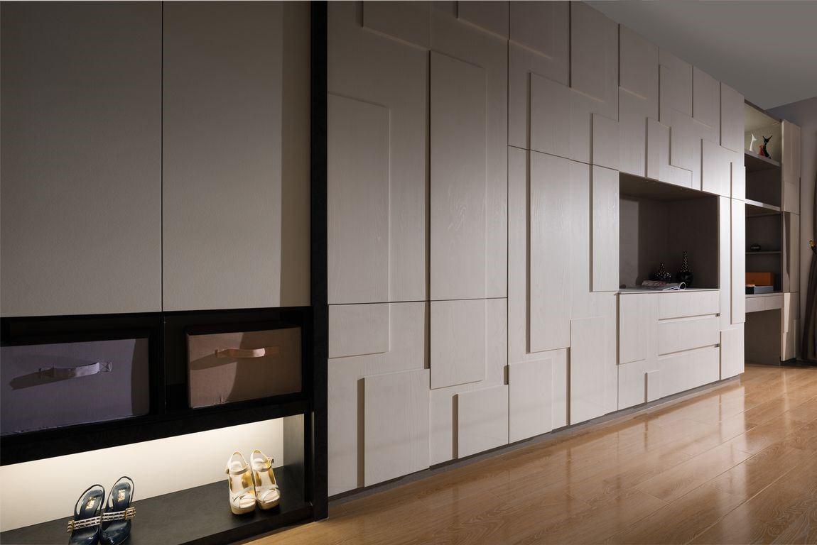 臥室內的大面積電視牆兼衣櫃,利用系統板材厚薄的高低差,營造時尚與收納機能兼具的多功能櫃牆。