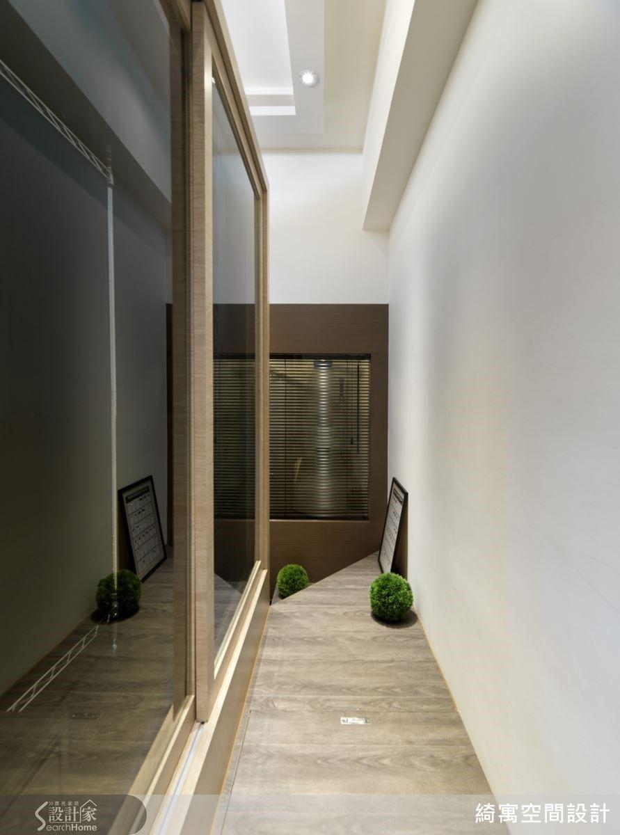 畫面左方的收納櫃,其實就是沙發背牆!張總監並以玻璃打造門片,讓空間感更顯放大俐落。