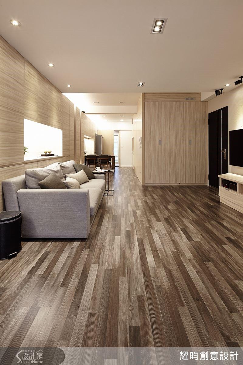 設計師重組格局,將客廳居中,收納櫃安置在屋子的兩側,再以水平同向紋路的地板配合長軸線的走向,避免垂直短促的切割,延伸景深效果,讓空間更為深邃。