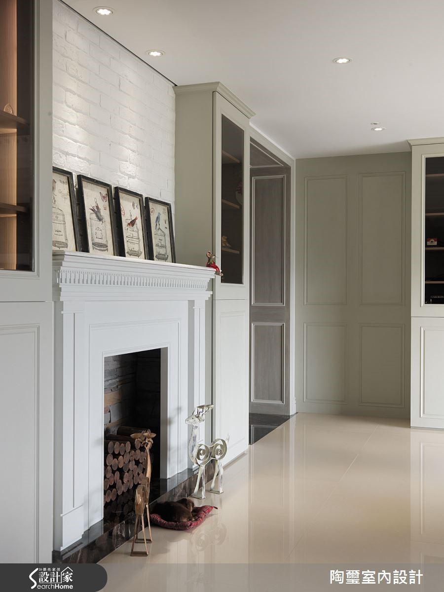 白色文化石牆襯著壁爐設計,在燈光的投射下隱現樸實溫馨的美感。