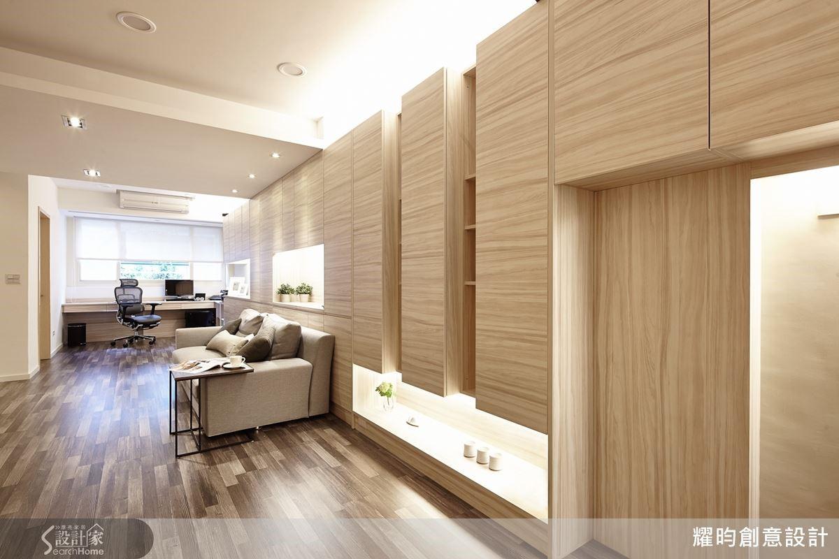 14 米的長型屋,居中明顯有著兩根大樑與柱,設計師以連續的展示收納櫃,將它統整為造型一致的立面,凹凸虛實的櫃體銜接天花樑體,讓它有著延伸而下的視覺效果。沙發背牆以系統櫃修飾,讓人完全分不出櫃子與柱子。