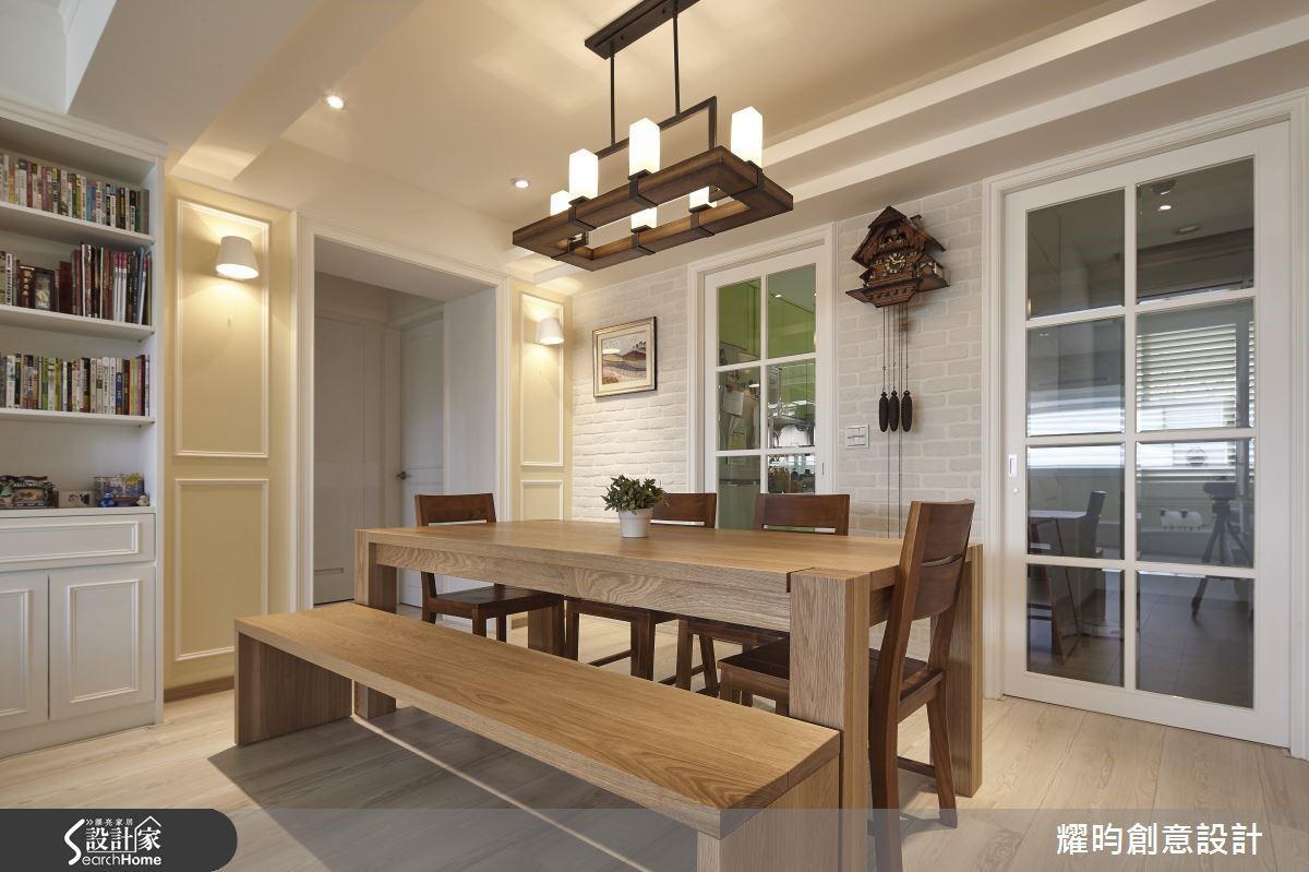 充滿鄉村風的餐廳,木桌的兩端正好是相對的兩根柱子,設計師以美式簡約的線板裝飾,並以對稱的造型牆面隱藏了小儲藏室,看不見畸零格局,只看見古典與優雅。