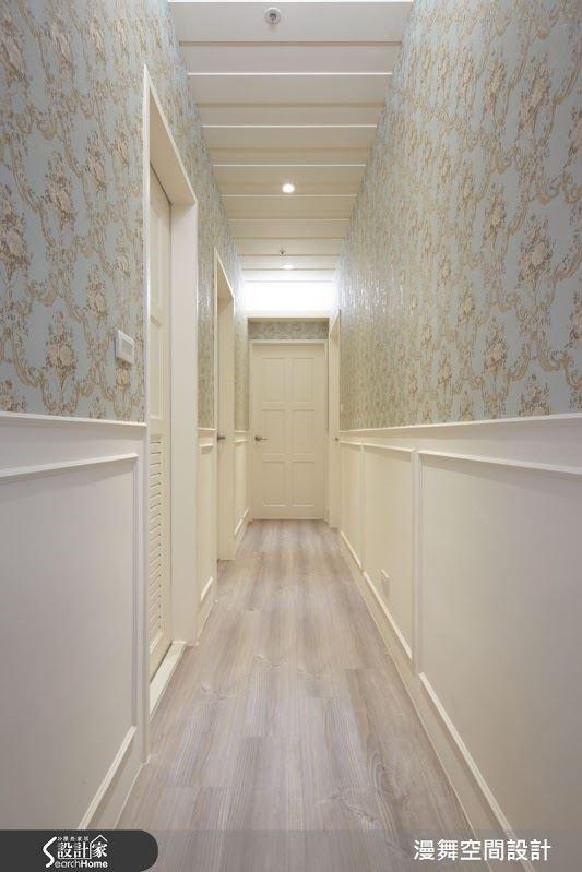 通往臥室的通道,兩側牆面以白色造型線板與淡雅的花卉壁紙勾勒出帶點鄉村質感的甜美氣息。