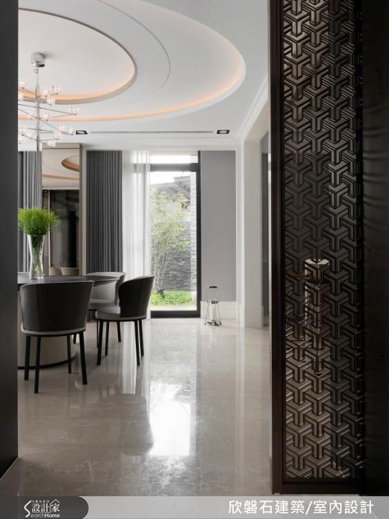 餐廳與客廳空間位於同一條軸線以穿透的電視牆與鈦金雷射切割格柵電動門區分,構成便利動線,雙面以大理石、鈦金屬與玻璃異材質銜接,整合展示收納,滿足兩個場域的雙功能性。