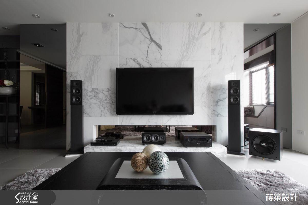 電視牆採用整塊石材切割後,再拼貼而成,因為紋理系出同源,反而比用一整塊石材來得靈活輕盈;左右兩邊以茶鏡裝飾,既可以放大視覺空間,增加光線反射,左邊的一扇同時隱藏1坪大的儲藏室入口,減輕視覺雜亂的機會。