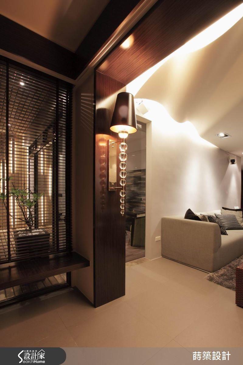 陽台與客廳之間,做出超寬的門框,其實是為了隱藏柱子以及電視牆的機櫃,特別挑選的大型壁燈成為亮眼裝飾,夜幕低垂時,整個空間瀰漫浪漫氣氛。