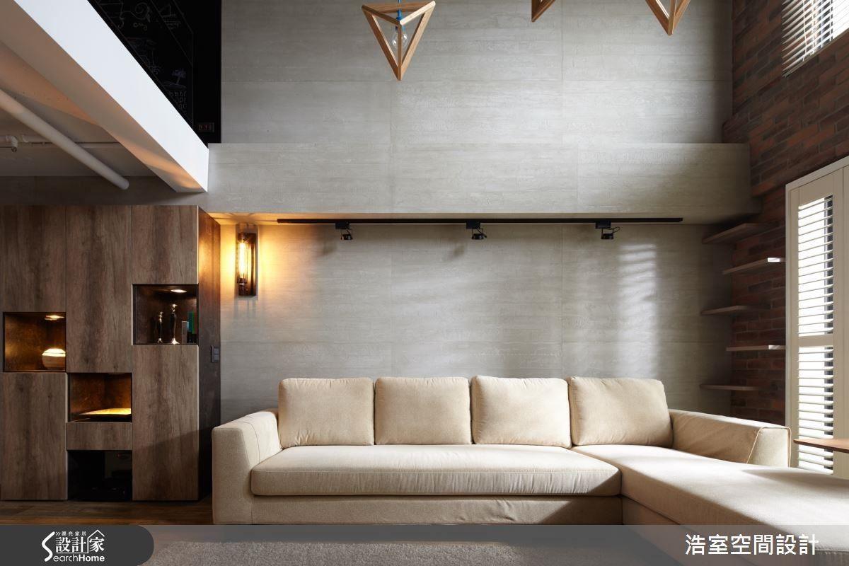 客廳主牆以水泥板裝飾,配合淺色的布質沙發柔化了原本粗獷的空間主調,強調木紋的展示收納櫃在燈光下,透露出時尚感。