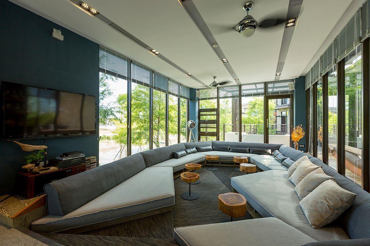 攝影_江建勳/客廳的面牆皆以強化玻璃取代,搭配百葉窗可自行決定室內光線的強弱;沙發為訂製的造型沙發,看似懸浮的構造呼應了樹屋的建築型態。