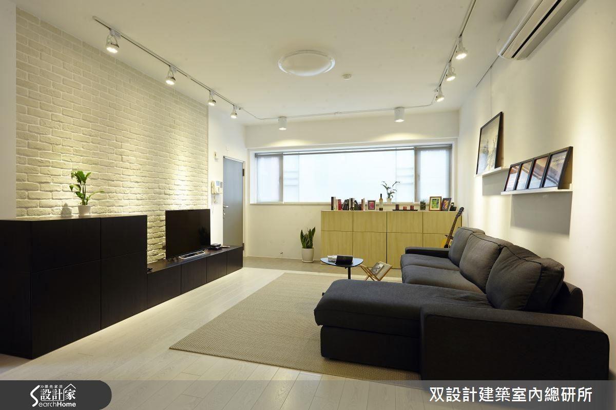 双設計_05個案中,黑色的電視櫃座,搭配黑色的布質沙發。獨具個性的黑白對比因為融入了些許的原木色而感覺溫馨。圖右,沙發背牆的兩道木層架,便於屋主陳列、更替小型畫作。