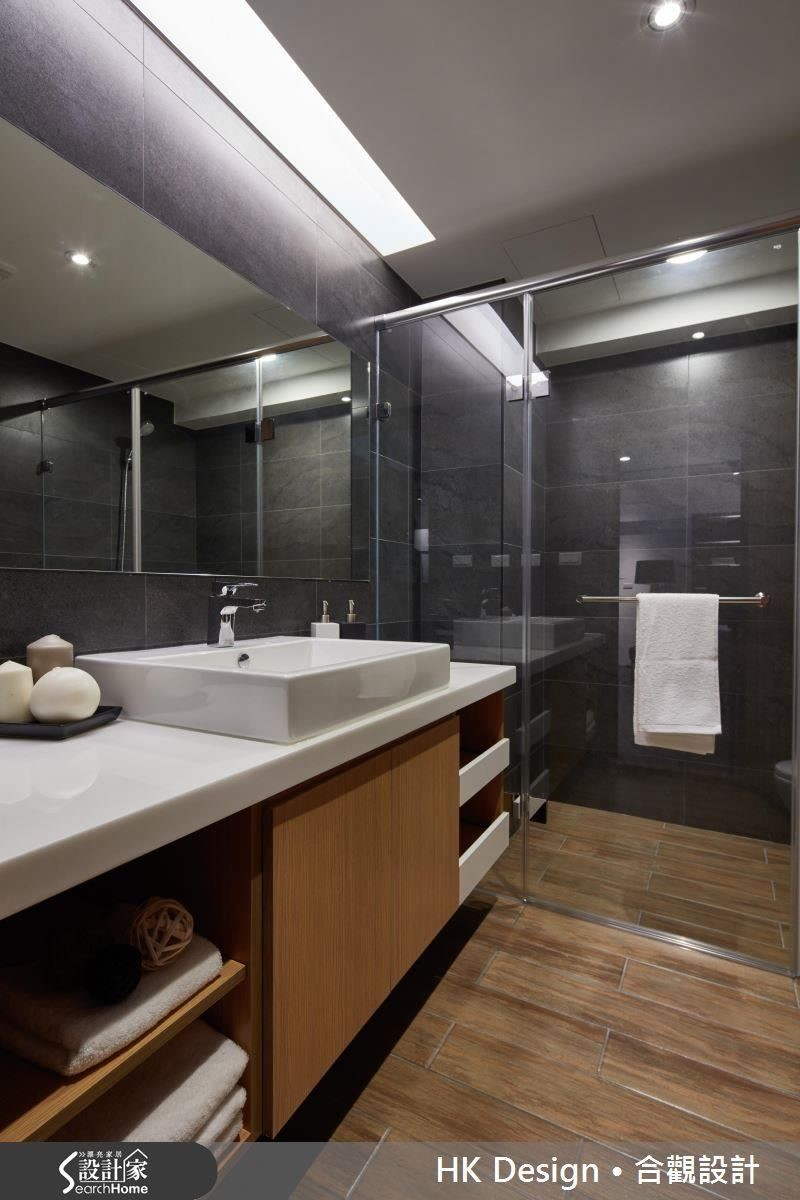 單身公寓合併原有的兩間小衛浴,讓衛浴空間更寬敞,並規劃成乾濕分離的空間。板岩磚牆搭配木紋地磚,展現屋主喜愛的美學風格。