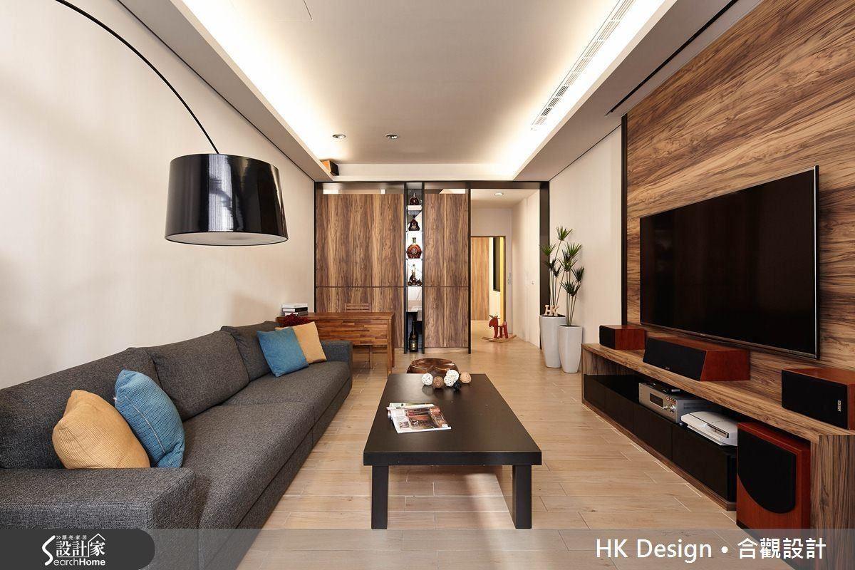 透天厝一樓的長型客廳,在樓梯間的側牆以天然木皮與鐵件打造一道落地櫃,除了收納雜物也收藏男主人的藏酒。