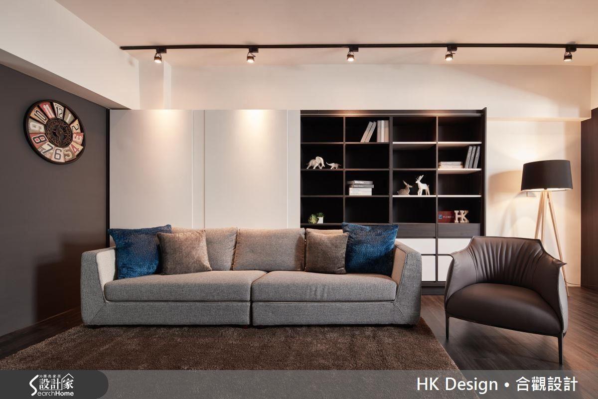 白色的沙發背牆不僅能烘托深色的家具,大片拉門跟櫃格並在開放及封閉之間構成簡約卻不單調的背景。
