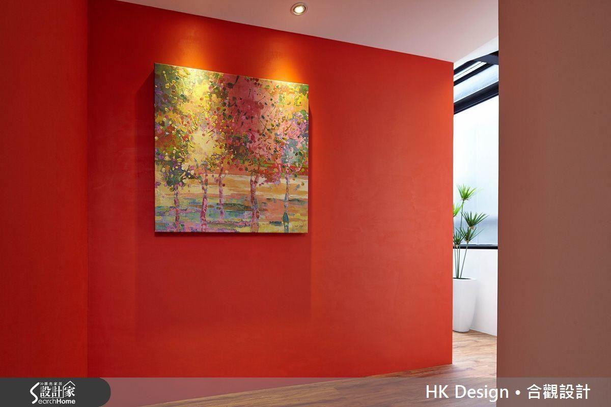 隔間牆刷成紅色,掛上畫之後再以燈光帶出氛圍,成為動線過程的一景。藉由跳色手法,在白牆環繞中的紅牆也在這個狹長軸線形成了一處端景。