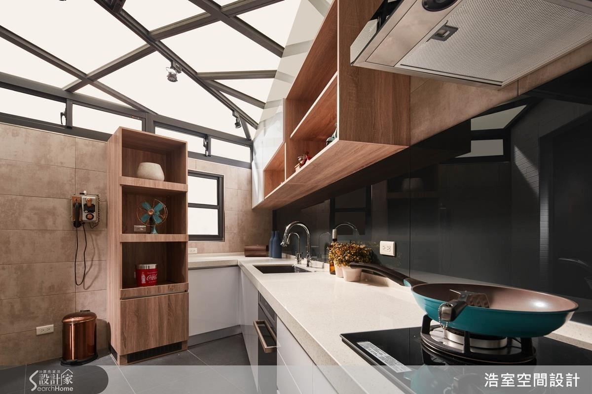 將廚房移住後院,加高圍牆高度後再加氣窗,就成為隱蔽的私人空間,上方天花板是透光性強的採光罩,配合地形做出倒勾狀的流理台,在廚房空間裡一點兒也不奇怪,反而符合料理動線。鐵灰色的烤漆玻璃呼應上方不規則金屬支架的深色,穩住空間氛圍。