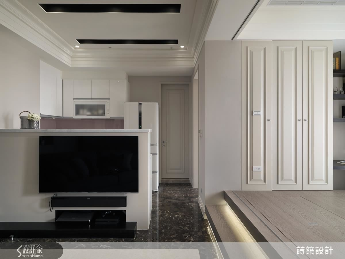 一進門就是客廳,利用廚房的半高吧台當隔間也兼電視牆,走道的寬度剛好增加沙發與電視的距離,又是一地多用的妙招。