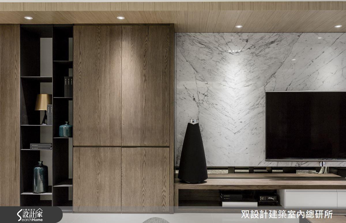 客廳主牆的左半部,運用深色的天然木皮及黑色鐵件打造出虛實交錯的落地櫃格;右半的電視牆,則利用大理石的天然紋理及簡練的底櫃造型來展現精煉的品味。
