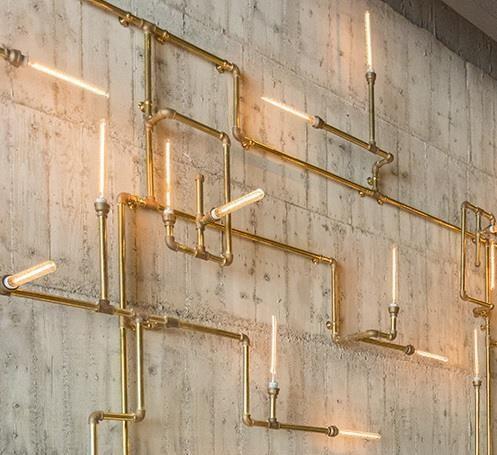 用餐區域有一道斑駁原始的水泥牆,牆面上有木板刻印的痕跡,江振誠保留牆面,用燈管綻放出牆面的溫 度,也營造了浪漫的用餐氛圍。