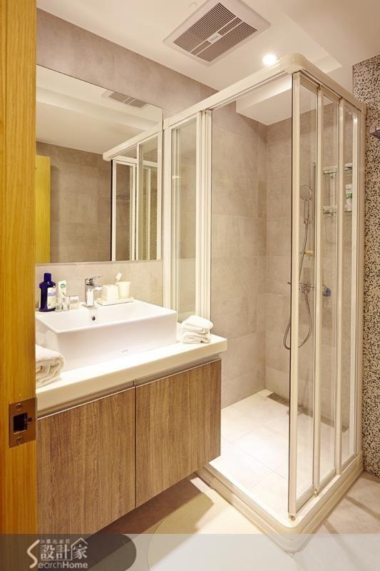 設計師為主臥衛浴間量身製訂了以系統櫃搭配人造石的浴櫃,出品味精煉又有收納機能。淋浴拉門乾濕分離的設計能讓整間浴廁更顯舒爽。