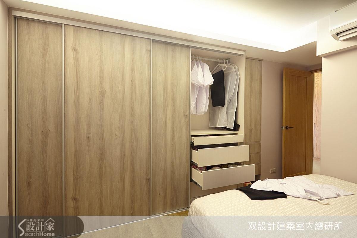 主臥面寬兩米三的大衣櫃整合了抽屜、吊掛衣架與儲物櫃。這道牆面的深度原本不足,略往客廳挪動了 15 公分之後,就能打造整排櫃體了。