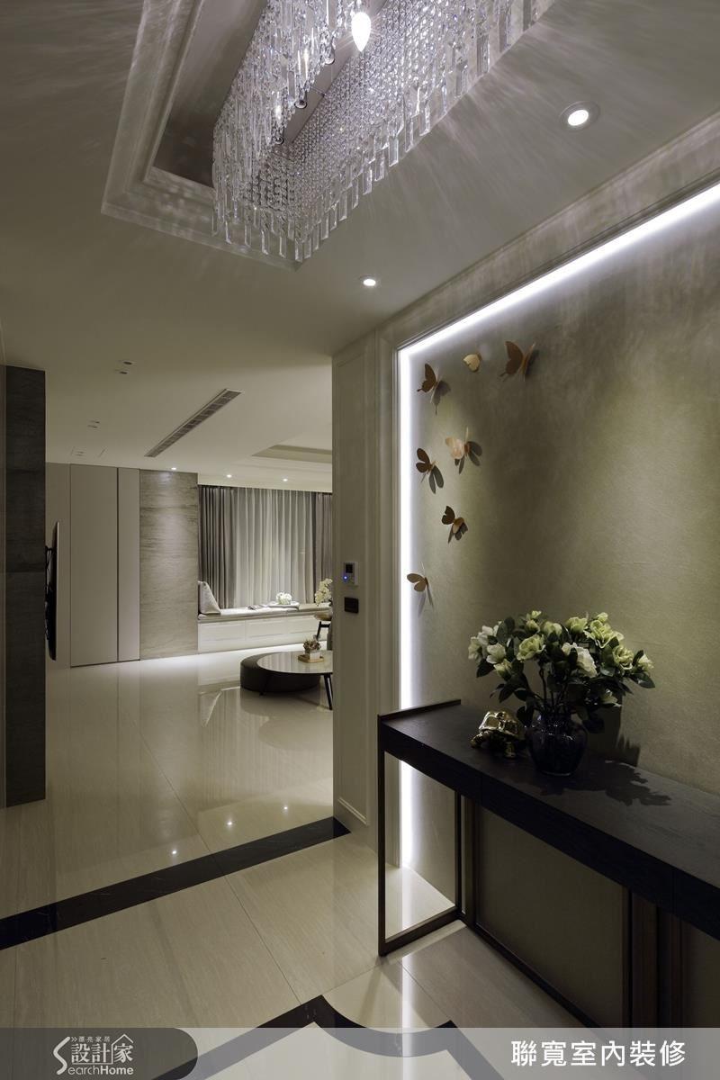 玄關進門處,水晶吊燈映在暖灰的主牆面,搭著象徵家徽的地磚,彷彿告訴你「歡迎回家」。