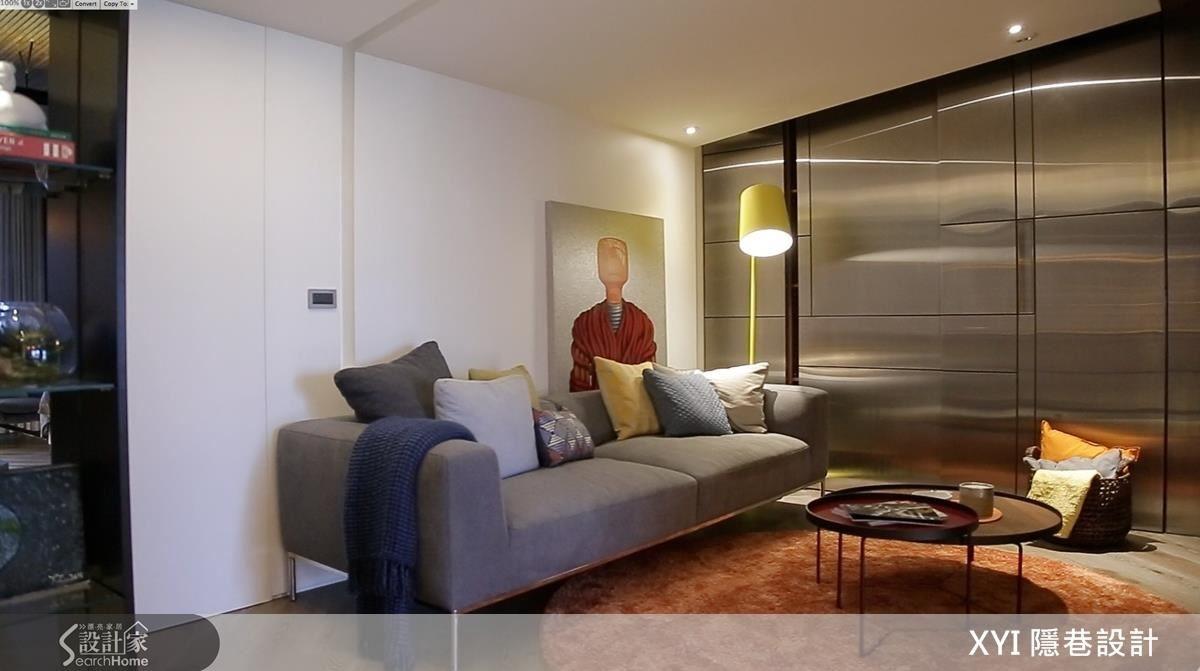 進入到夫妻的套房空間,修飾空調的斜屋頂下是溫馨的小客廳。金屬風的不鏽鋼收整櫃體與門,也讓空間更有延伸感。