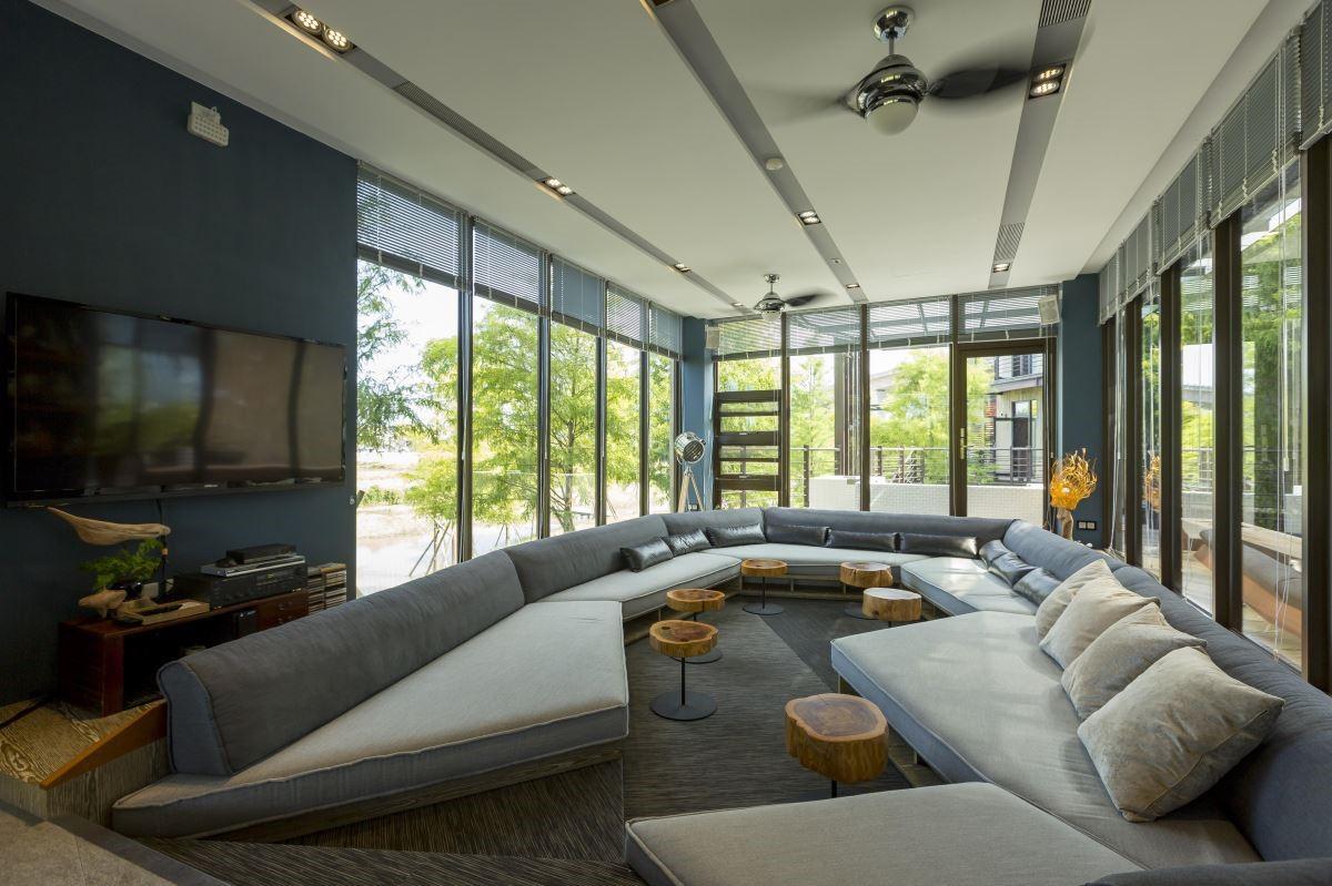 1F 外部打造成 L 型露臺,百葉窗簾的運用,讓光線能自由穿透進屋子,環繞其中,訂製的沙發,散發出屋主好客熱情的心。