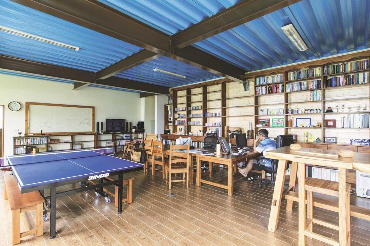 地下室天花板其實是1樓的鋼筋地板,刻意裸露再刷上藍色油漆,非常醒目。整排書牆是男主人的傑作,高腳吧檯是可以小酌的角落。攝影_葉勇宏