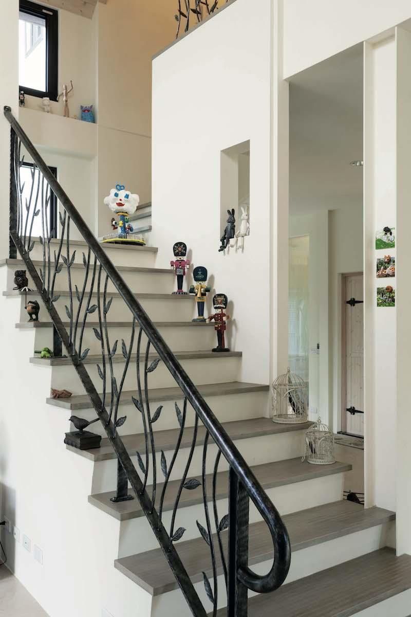 通往二樓的鍛鐵扶手,是女主人對安全與美感的堅持。梯上的擺飾,全由她親手佈置,部分單品甚至是她與女兒手工製作、彩繪而成。攝影_Yvonne