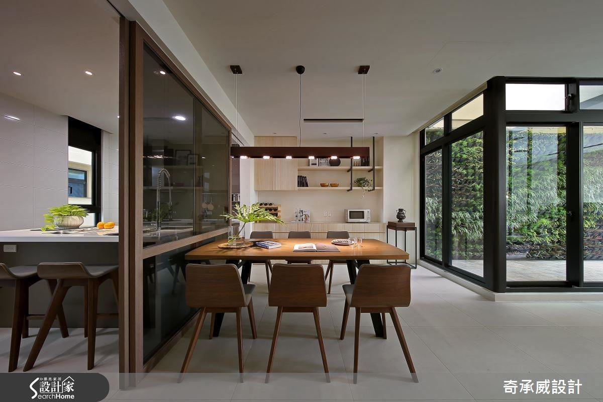 二樓是客廳、餐廳與廚房空間,餐廳與吧檯隔著灰玻連成一線,營造一種相對映的趣味。