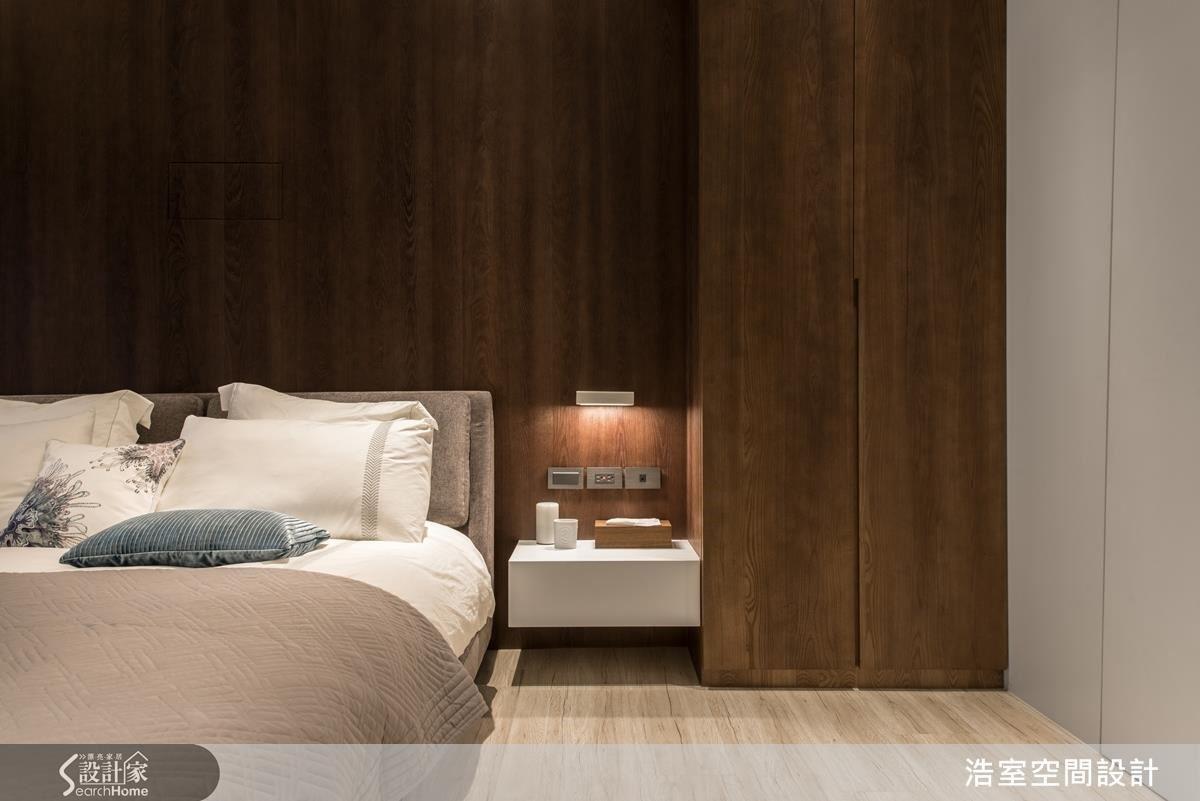 業主要求主臥能像飯店般舒適無壓力,浩室團隊一改公共空間的白色主調,以木紋打造出較為沉穩的氛圍。木紋的床頭背牆簡單而有深度,相當成功的對花技巧,隱藏了投影機的設備;而白色小床頭櫃上方設計感十足的電源開關,以及無把手設計的小型衣櫃,細節的講究,成功打造高質感的主臥空間。
