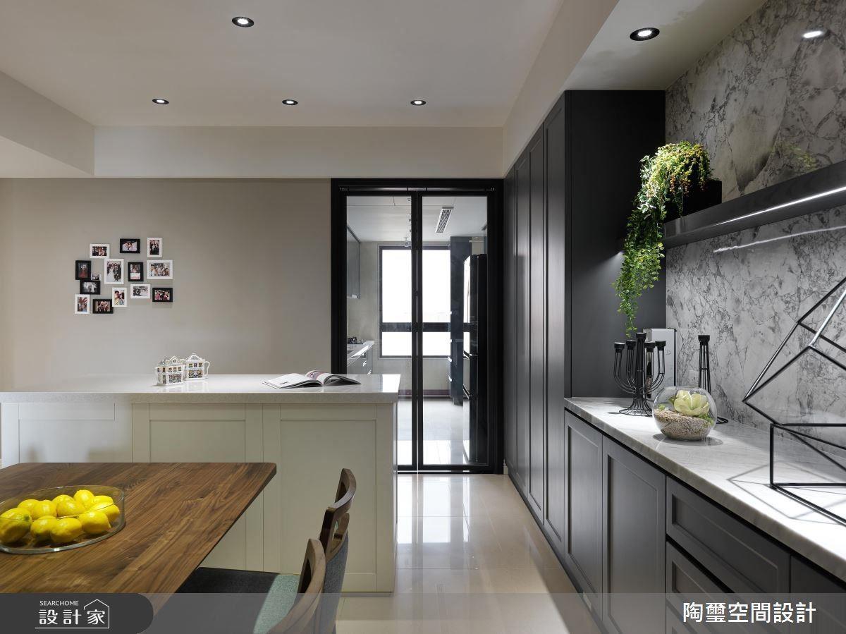 廚房以玻璃門片保留透光性,也阻隔油煙溢散的可能,外部則延伸一道大中島,完美實現女屋主的夢想。