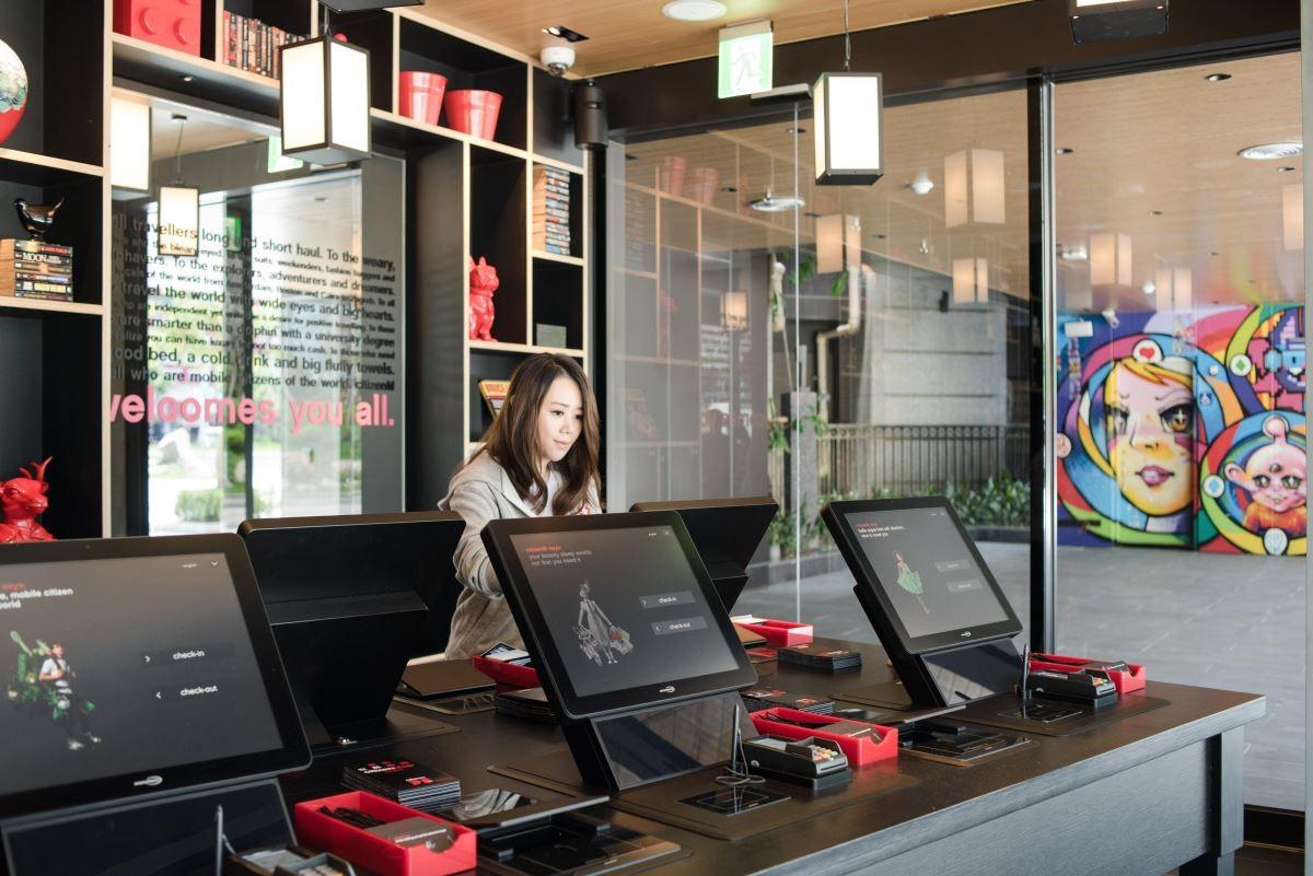 與傳統酒店不同,大廳少了服務櫃台,卻有可一次提供 6 位旅客登記的電子櫃位,以及一位 citizenM 大使,指導住客完成入住手續。(攝影:沈仲達)