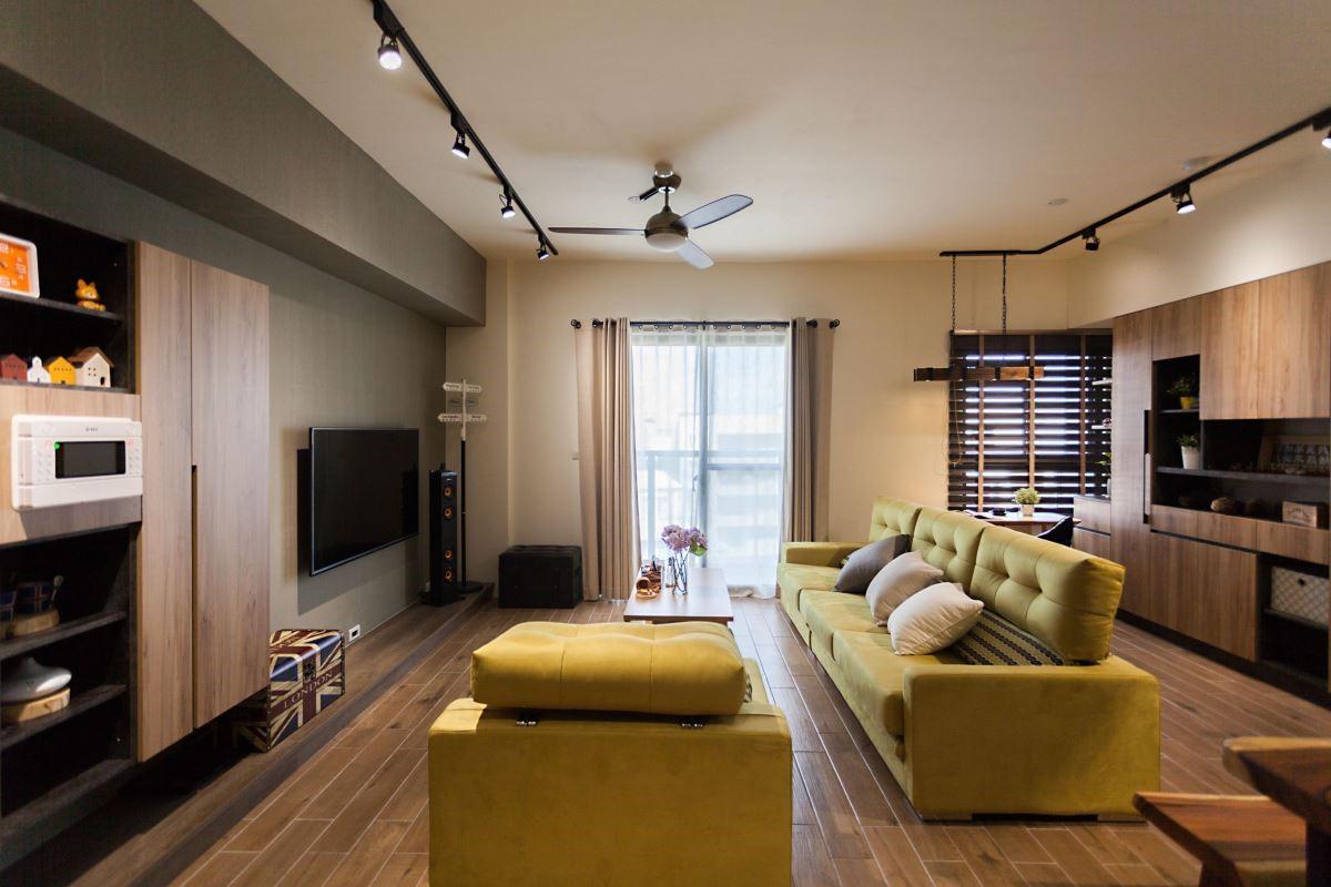 以系統板材的材質與色彩比例形成多元變化,灰色電視牆搭配木紋板材及黑色層板,虛實相間,由淺入深的與工業風軌道燈融合。