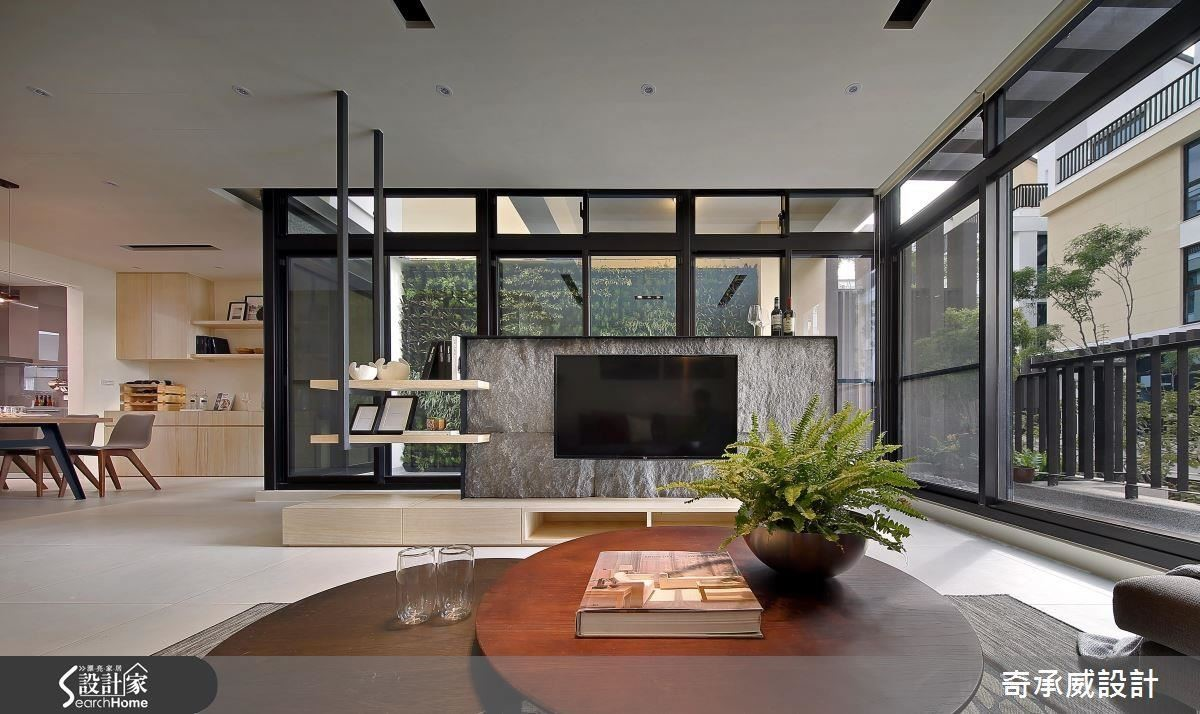 增拓開窗面積,將日光大量引入室內,提升視覺明亮度,並利用玻璃隔間的配置,導入戶外植栽牆綠意引入室內,搭配著鑿面石皮所構築的電視牆,引入源源不絕的自然生命力。