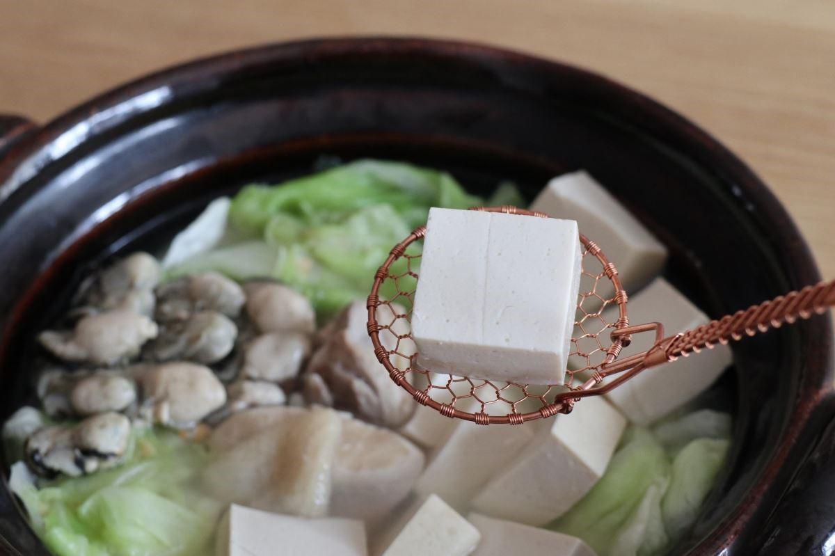 細密手工編織的金網つじ紅銅豆腐勺,把香噴噴的鮮香白菜雞湯裡,煨得甜甜暖暖的豆腐,一塊、一塊,優雅完整地盛起。