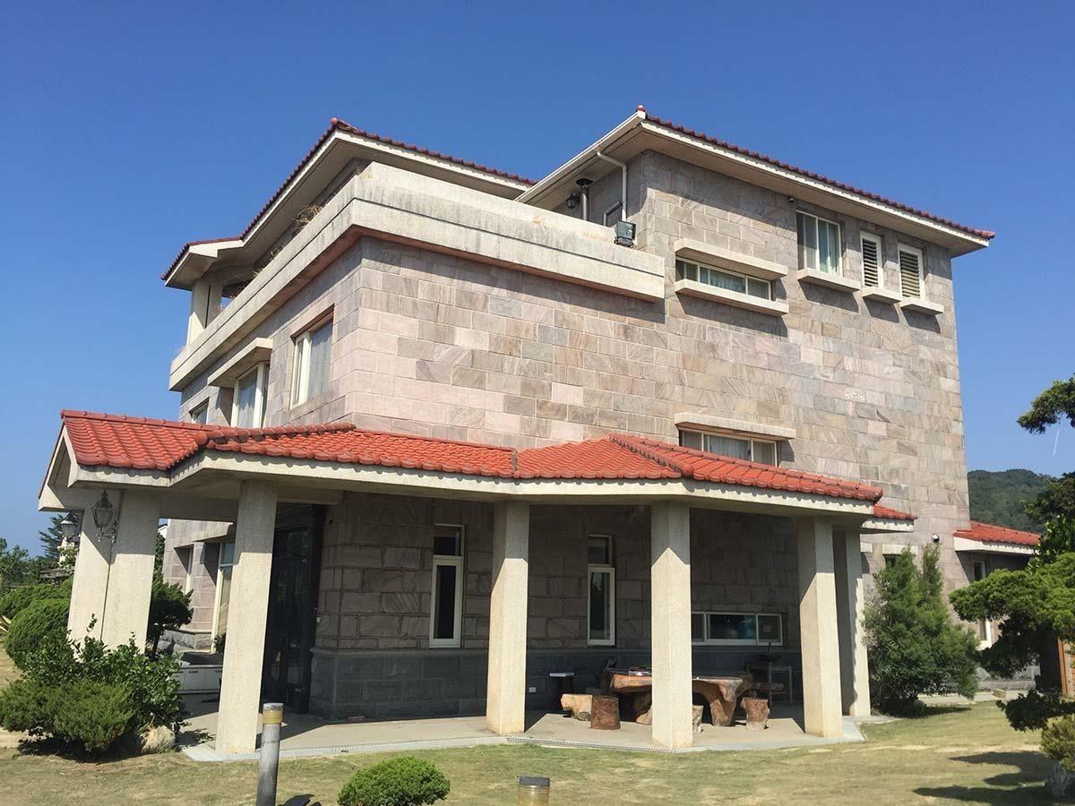 濱海的獨棟別墅原來的外牆面貼石材磚,歷經海風侵蝕逐漸剝落,屋主為此甚為煩惱。